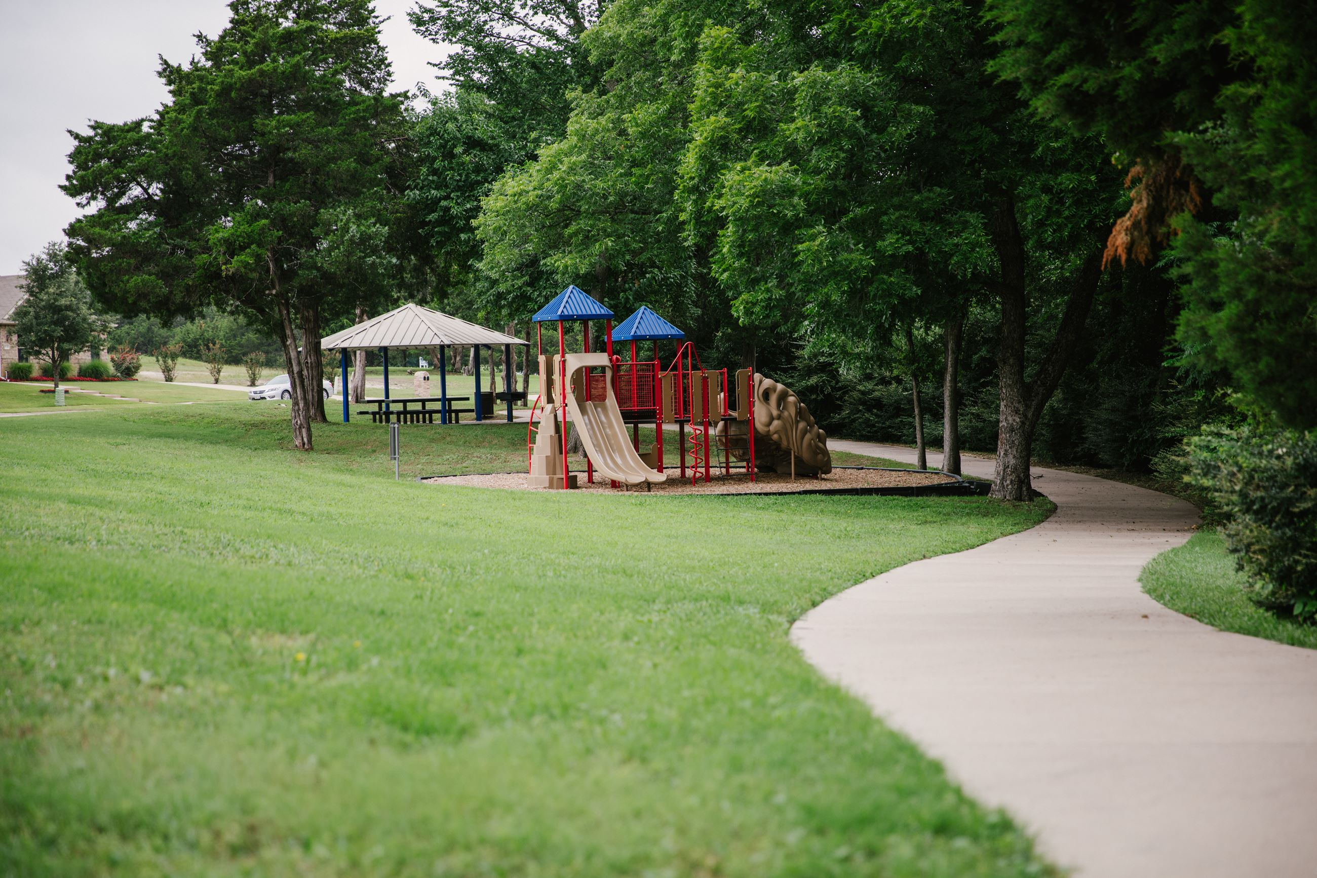 Play structure, pavilion, and trail at Wooded Creek Greenbelt