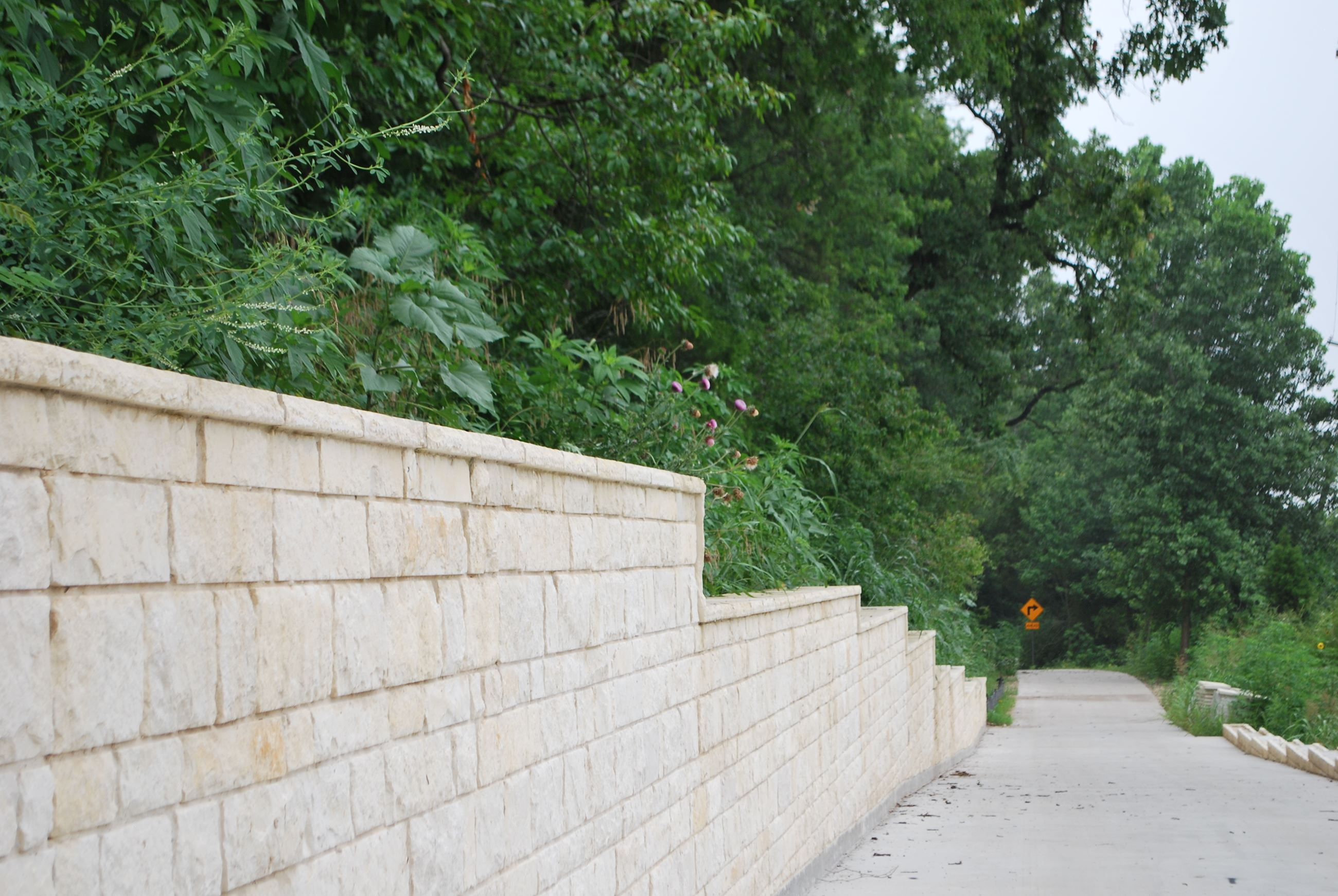 Granite wall along paved trail.